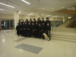 Graduation photo featuring Dr. Greer and the service dog Bahari