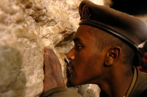 Close up photo of Ethiopian member of the Israel Defense Forces kissing the Western Wall in Israel.