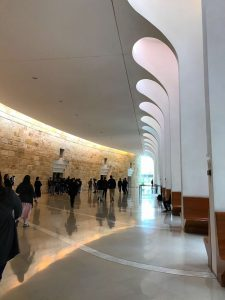 Interior view of a hallway in the Isralei Supreme Court Building with natural light strwaming in from a row of windows.