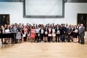 A group of twenty students and faculty pose holding certificates at the Closing Ceremony in Giessen, Germany.