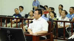 Chinese lawyer Jiang Tianyong sits in front of a microphone during his trial.