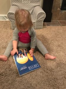 A young child sits on the floor looking at a copy of the Marquette Lawyer magazine.