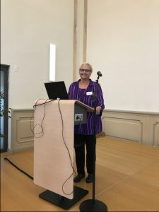 Professor Janine Geske standing at a podium with an open laptop as she addresses an audience in Germany.