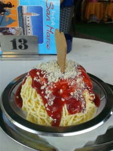 A plate of gelato ice cream shaped like spaghetti noodles and covered in red sauce.