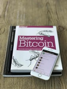 Photo of a Bitcoin Cash wallet on a mobile phone and a copy of Mastering Bitcoin written by Andreas Antonopoulos