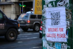 Photo of a lampost with a paper flyer taped to it asking passerby to send bitcoins to pay for college.