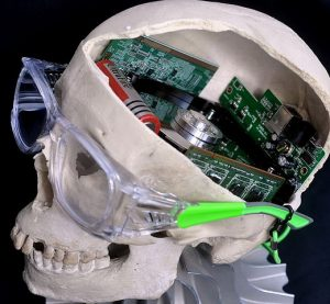 Photo of a model of a human skull with the top of the skull removed, revealing computer circuitry inside.