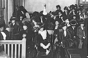 A courtroom is filled with women dressed in long black dresses and wearing hats.