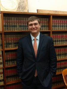 Stduent Scott Lyon, dressed in a suit, stands in front of a bookcase holding law books.