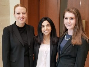 three women, all law students, stand in front of a courtroom door