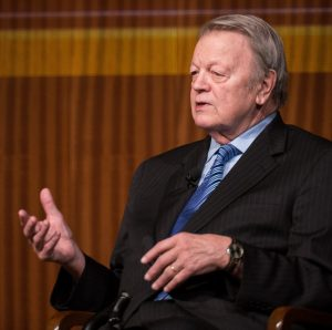 Author Garry Wills dressed in a suit and tie speaks at a public event.