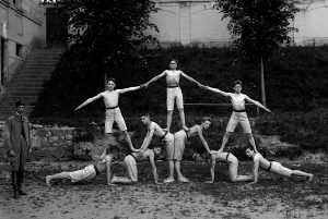 Black and white photo of a group of men in gymnast uniforms in a formation where some stand on the shoulders of others.