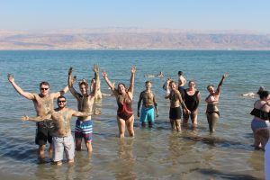 Law students in bathing suits stand and wave in the waters of the Dead Sea.