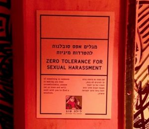 """A paper flyer posted to a wall urges """"Zero Tolerance for Sexual Harassment."""""""