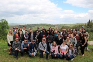 About 40 law students pose in casual clothes with the green hills of Israel in the background.