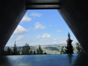 View looking out over the Israeli countryside of rolling hills and trees from within the Holocaust Memorial.