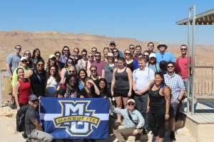 About twenty young people in casual dress surround a Marquette University flag at Masada in Israel.