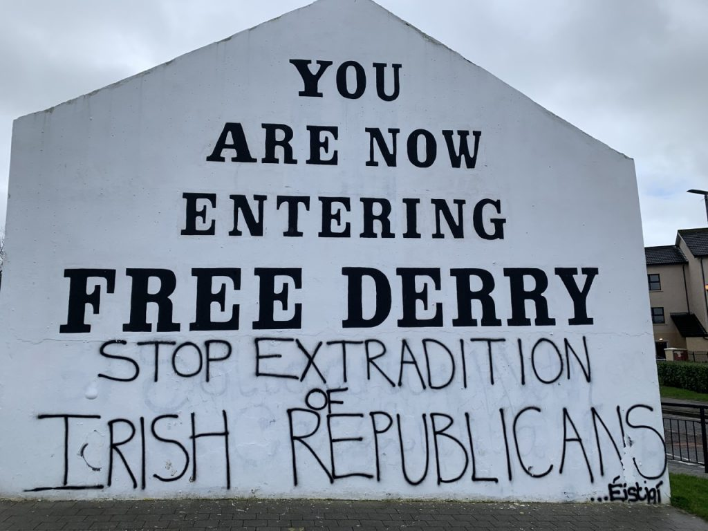 """image of sign, it reads, """"YOU ARE NOW ENTERING FREE DERRY"""" followed by the graffit """"STOP EXTRADITION OF IRISH REPUBLICANS"""""""