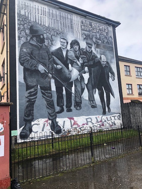 image of mural, depicts an injured protestor being carried by others