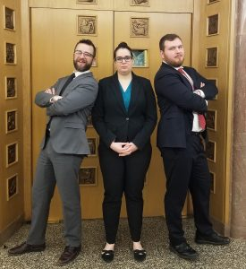 3 law students posing in a courthouse in professional dress