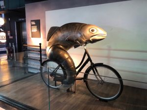 A piece of art depicting a fish on a bicycle