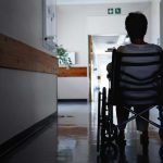 person sitting in wheelchair in empty nursing home hallway